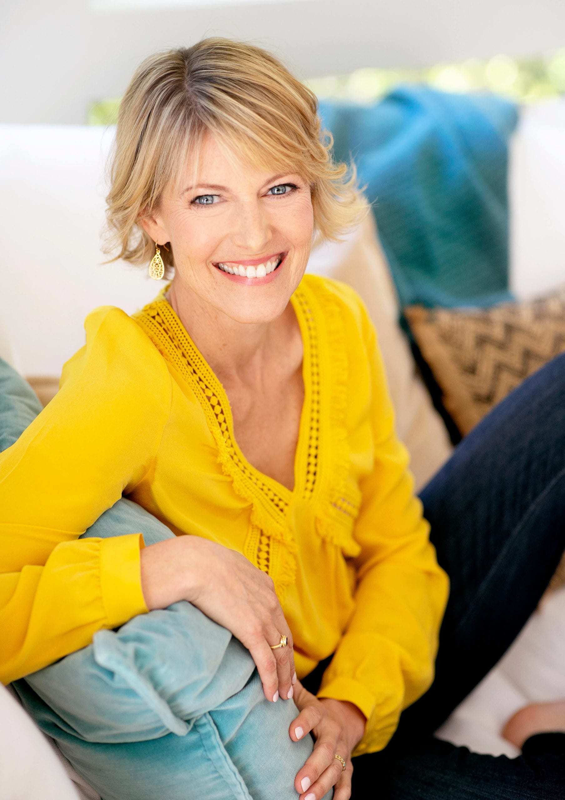 Elizabeth Hunter Diamond, professional clairvoyant and energy healer, sitting on white couch with teal blue pillows.