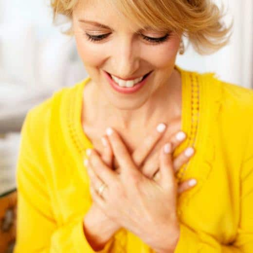 Elizabeth Hunter Diamond, clairvoyant energy healer, in yellow shirt with hands on heart, teaching manifesting love.