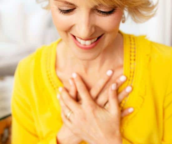 Elizabeth Hunter Diamond, clairvoyant energy healer, in yellow shirt with hands on heart, teaching manifesting love.
