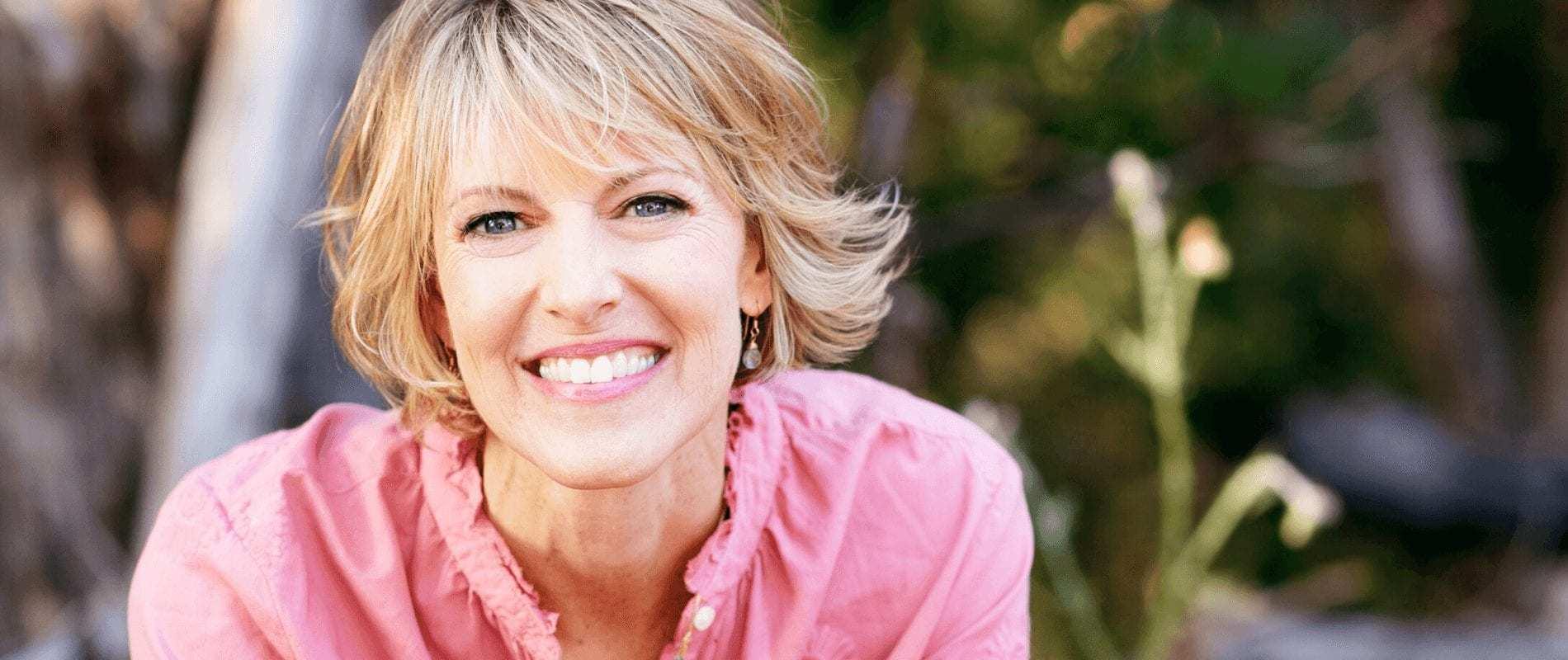 Elizabeth Hunter Diamond, clairvoyant & psychic energy healer, smiles in pink shirt.