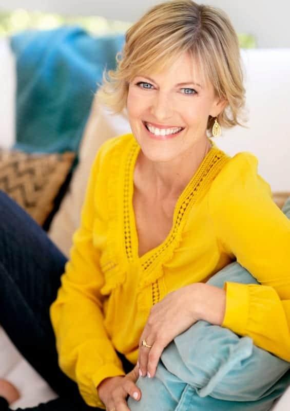 Elizabeth Hunter Diamond, psychic energy healer sits on white couch.