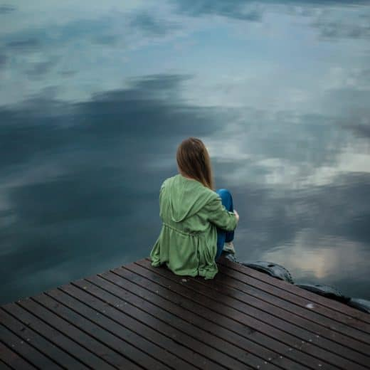 Woman unlucky in love and single sitting on a dock