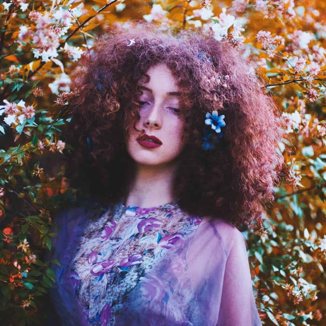 Woman healing from heartbreak, stands with her eyes closed and is surrounded by flowers.
