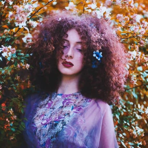 Woman healing her blocked heart chakra, stands with her eyes closed and is surrounded by flowers.