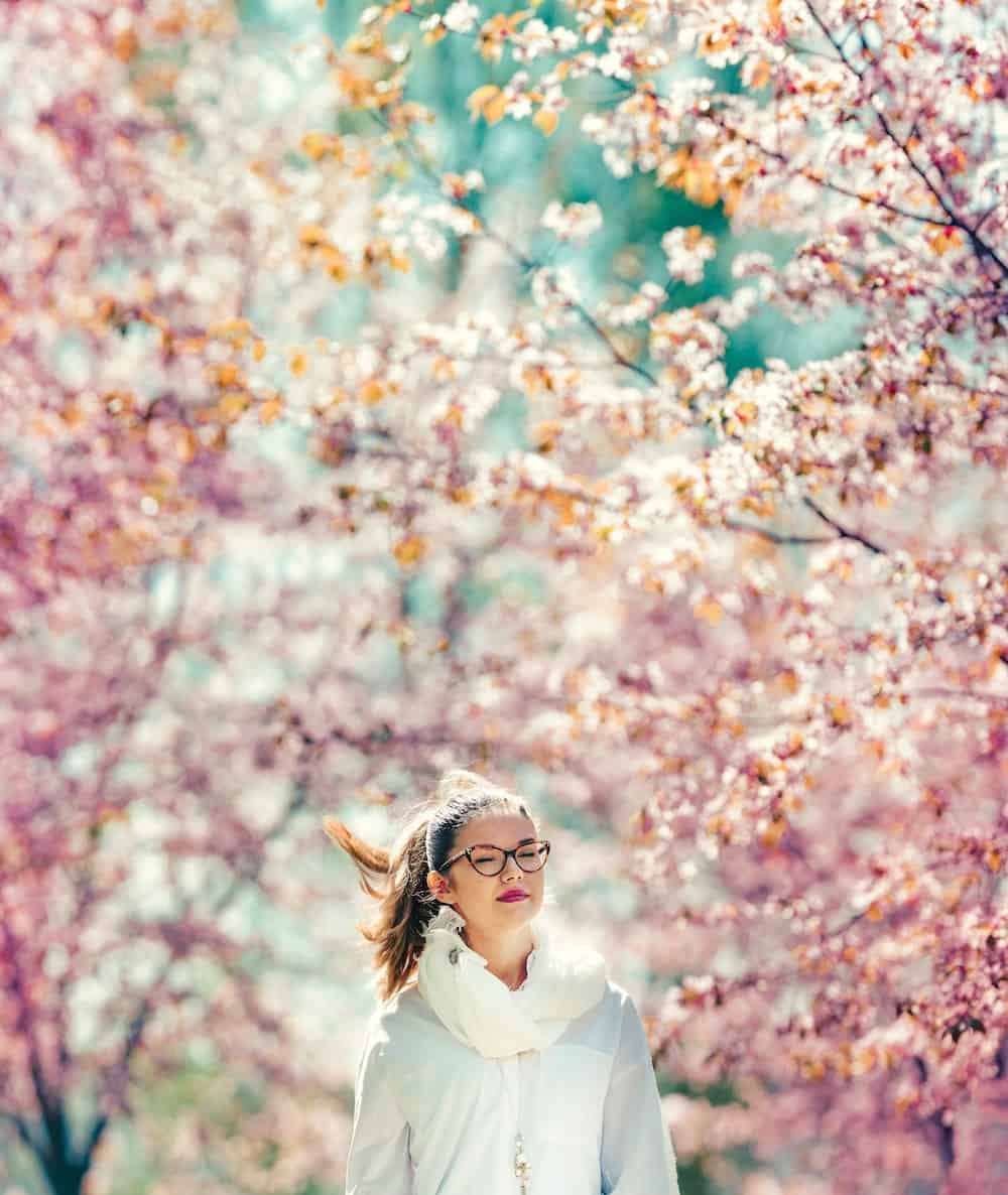 Being an empath, woman walks among the cherry blossoms.
