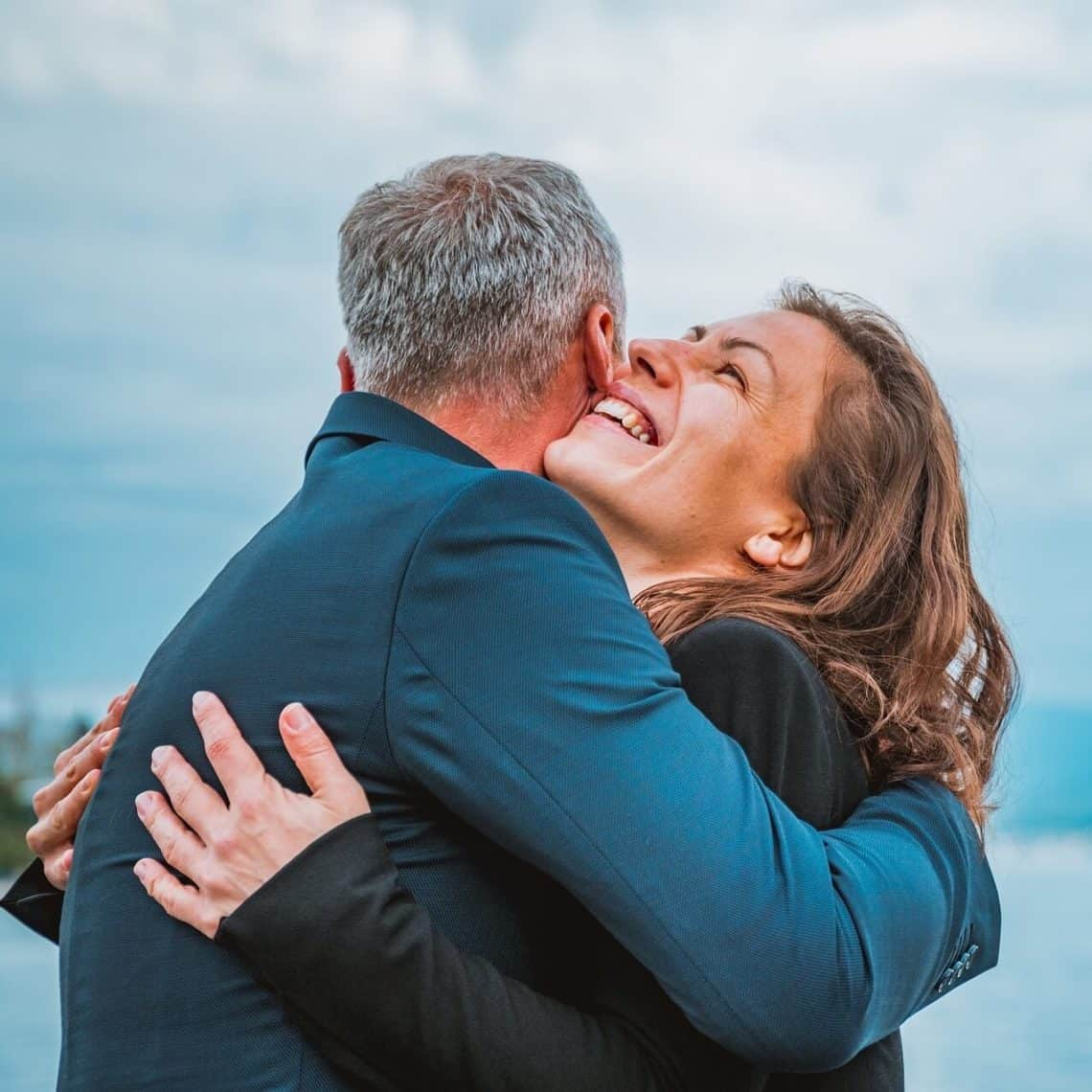A happy couple hugs and smiles under a blue sky. When you release your self-limiting beliefs, you open your heart and let more love into your life.