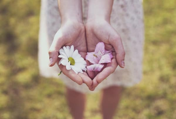 Woman being an empath, holding white and pink flowers in her palms.