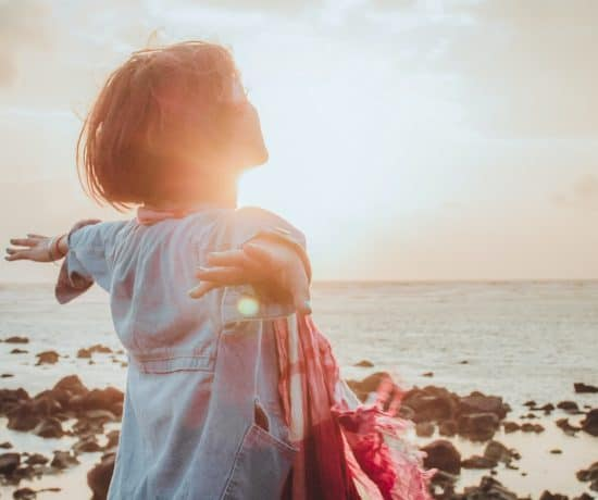 Empath woman stands on the beach with her arms wide open and basks in the sunlight. When you set energy boundaries you protect your empath heart.
