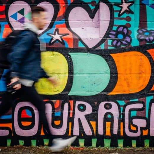 """A wall of colorful graffiti with """"courage"""" spelled out."""